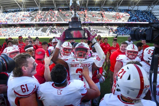 Ravi Alston of St. John's holds the Holy Grail traveling trophy following the Johnnies' win over St.Thomas Saturday, Oct. 19, 2019, at Allianz Field in St. Paul.