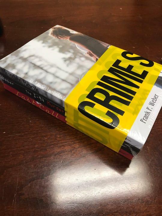 Books by local author Frank Weber, packaged in crime scene tape, are displayed in his Sartell office Tuesday, Oct. 15, 2019.