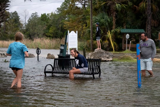 Rebekah Hanser sits on a bench waiting for her daughter Amelia Dropco, 15, to a take a photo of her. Mike Hanser and his son Issac Dropco, 12, make their way through the flooded streets of St. Marks, Florida as Topical Storm Nestor moves through the Panhandle.