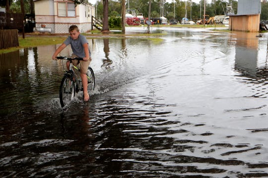 A child rides his bike through the flooded streets of St. Marks, Flordia, on Saturday, Oct. 19, 2019.