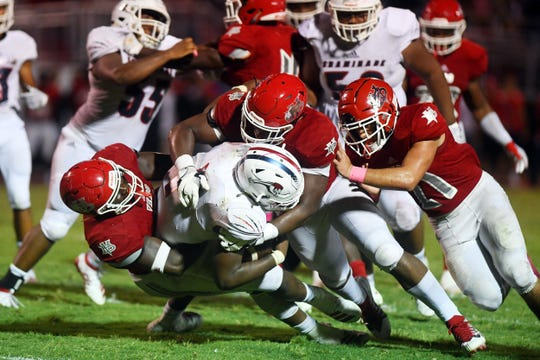 Vero Beach defenders make a stop in the backfield against Chaminade-Madonna on Oct. 18, 2019. Vero Beach hosts Deerfield Beach in the Region 3-8A final on Friday.