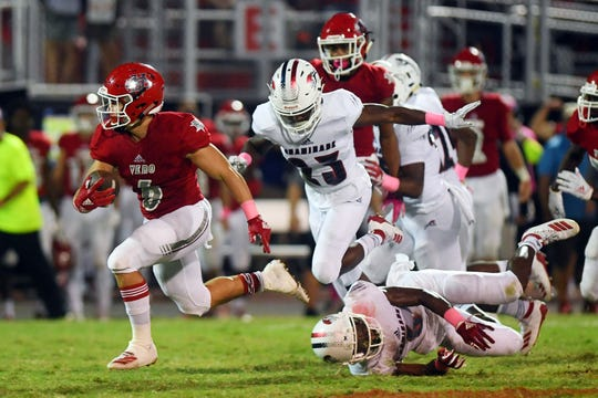 Vero Beach High School's Jaden Maizinger picks his way through the defense of Chaminade-Madonna defenders on Friday, Oct. 18, 2019, during a game at the Citrus Bowl in Vero Beach. The Fighting Indians went on to win the game 21-0 to match the state record of 60 regular-season game wins.