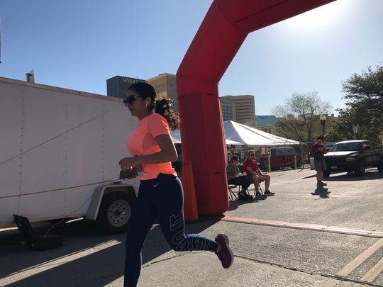 "Elizabeth Estrada was the first woman over the finish line in the ""Running of the Bulls"" 5K in Downtown El Paso on Saturday, Oct. 19, 2019."