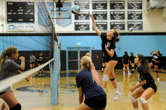 Emily Martin drills the ball back over the net during Buena High's practice Friday.