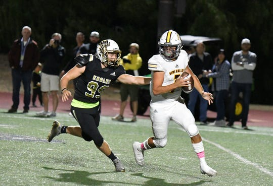 Oak Park's Dylan Natcher chases after Simi Valley quarterback Travis Throckmorton during the Eagles' 31-7 victory on Friday night in a Canyon League opener.