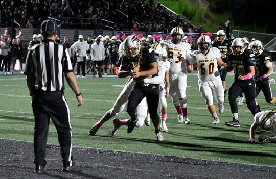 Oak Park High quarterback Gianni Smith carries a Simi Valley defender to the end zone for a touchdown during the Eagles' 31-7 victory on Friday night in a Canyon League opener.