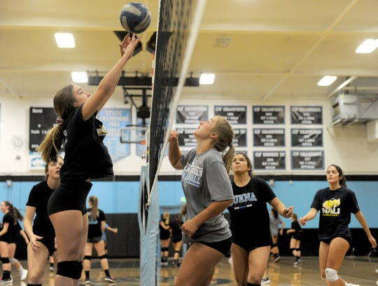 Brooklynne Harrington, left, rises over the net with teammate Caylie Button, right, looking on during Buena High's practice Friday.