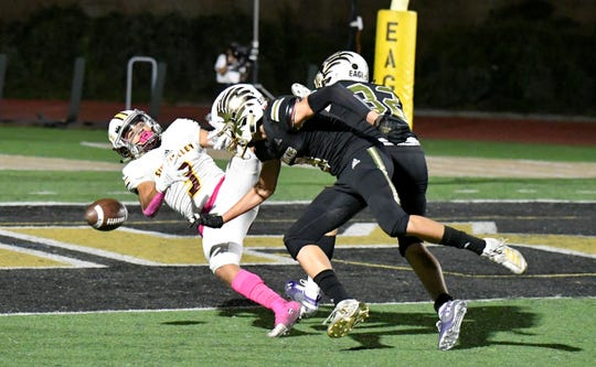 Simi Valley High receiver Malik Hunt has the ball knocked loose by two Oak Park defenders during Friday night's game. The Eagles won 31-7 to improve to 8-0 and 1-0 in the Canyon League.