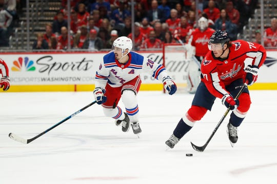 Washington Capitals right wing T.J. Oshie (77) skates with the puck was New York Rangers center Chris Kreider (20) chases in the second period at Capital One Arena on Oct. 18, 2019.