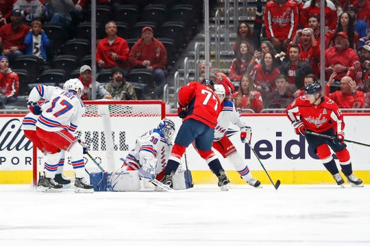 Oct 18, 2019; Washington, DC, USA; Washington Capitals right wing T.J. Oshie (77) scores a goal on New York Rangers goaltender Henrik Lundqvist (30) in the first period at Capital One Arena. Mandatory Credit: Geoff Burke-USA TODAY Sports