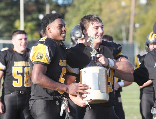Nanuet captains Justin Haughton (5), left, and John Kiernan (59) hoist the trophy after defeating Pearl River 34-19 in the 'Little Brown Jug' game at Nanuet High School on Saturday, October 19, 2019.