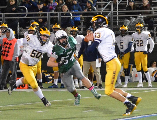 Brewster nose tackle Franco Milano closes in on Pelham quarterback Carlo Volpe in the first quarter of a 49-14 win by the Bears in a Class A playoff qualifier at Brewster High School on Oct. 18, 2019.