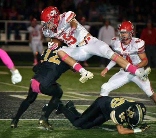 Holliday's Crae Jackson (19) is hit by Henrietta's Connor Mitchell (12) after hurdling Matthew Mills (56) in second quarter action Friday night in Henrietta.