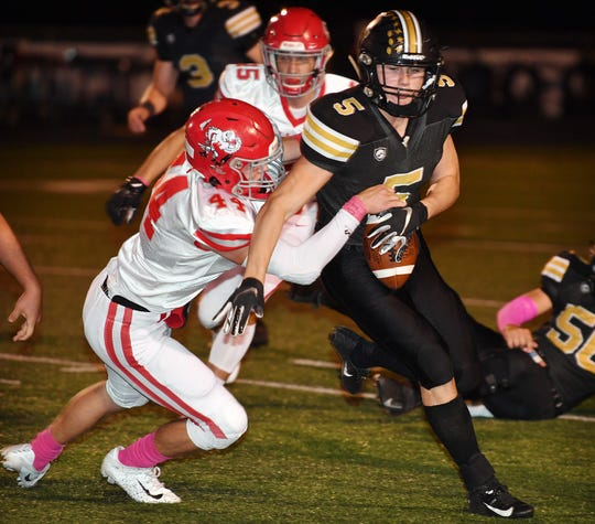 Holliday's Crosby Jurecek (44) attempts to strip the ball from Henrietta's Carson Cody (5) during Friday night's game in Henrietta.