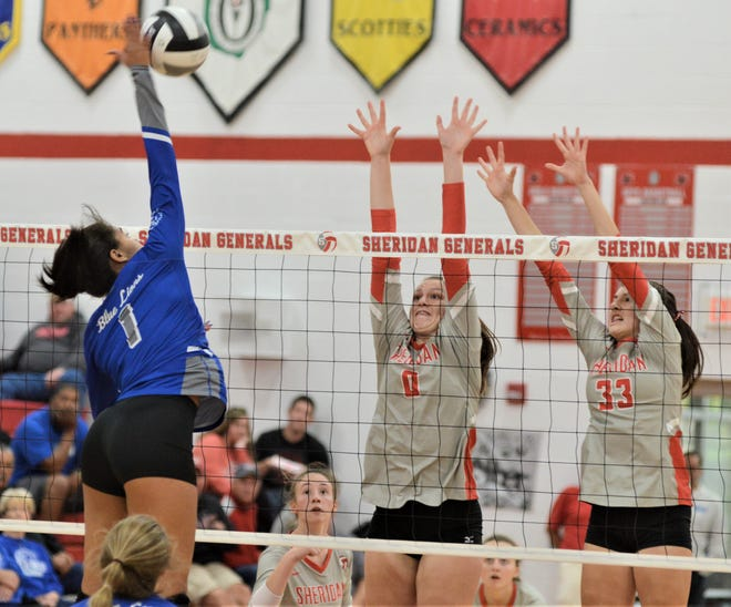 Sheridan's Faith Stinson (0) and Ally Perkins (33) try to block a shot from a Washington Court House player in Saturday's Division II sectional final. The Generals won in three sets.