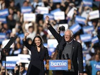 2020 Democratic presidential hopeful US Senator Bernie Sanders (D-VT) and representative Alexandria Ocasio-Cortez (D-NY) wave to a crowd of supporters during a campaign rally on October 19, 2019  in New York City.