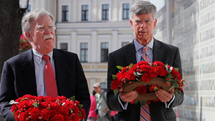 John Bolton (L), the US National Security Advisor and William Taylor (R), the US Ambassador to Ukraine, lays flowers to a wall with portraits of Ukrainian soldiers who were lost in the Eastern-Ukrainian conflict near of the St. Mikhail Cathedral in Kiev, Ukraine, 27 August 2019.