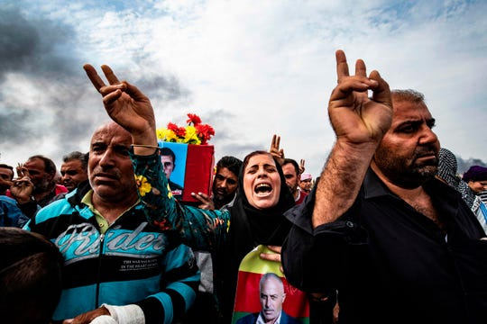 In an Oct. 19 photo, mourners in a cemetery in Tal Tamr attend the funeral of civilians and fighters who died during attacks by Turkish-led forces on the border town of Ras al-Ain.