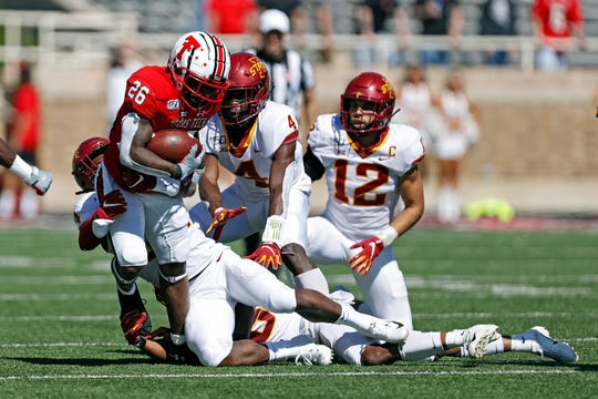 Texas Tech running back Ta'Zhawn Henry tries to break from Iowa State's D.J. Miller during the second half.