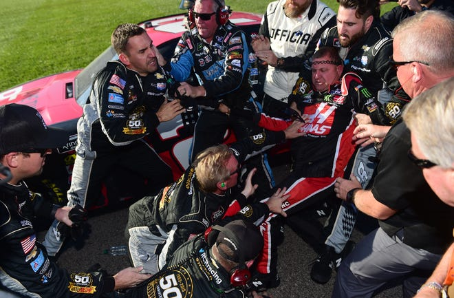 Crew members for Tyler Reddick and Cole Custer try to separate the two drivers during an altercation on pit lane following the Kansas Lottery 300 on Saturday.