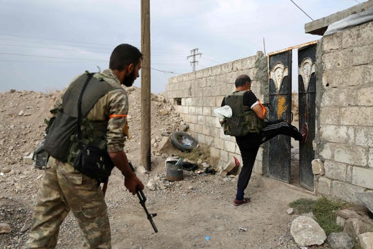 Turkey-backed Syrian fighters break open the front door of a house at a position that they are holding in the Syrian border town of Ras al-Ain on Oct. 19, 2019.
