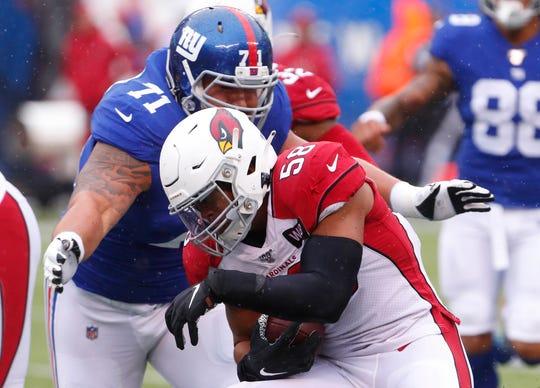 New York Giants offensive guard Will Hernandez (71) tackles Arizona Cardinals middle linebacker Jordan Hicks (58) after intercepting a pass during the first half at MetLife Stadium.