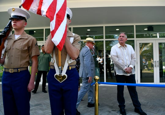 Chargé d'Affaires John Law for the U.S. Embassy looks above the flags carried by the U.S. and Philippine Marine honor guard before cutting the ribbon to open the new Visitor Center at the Manila American Cemetery Oct. 19, 2019.