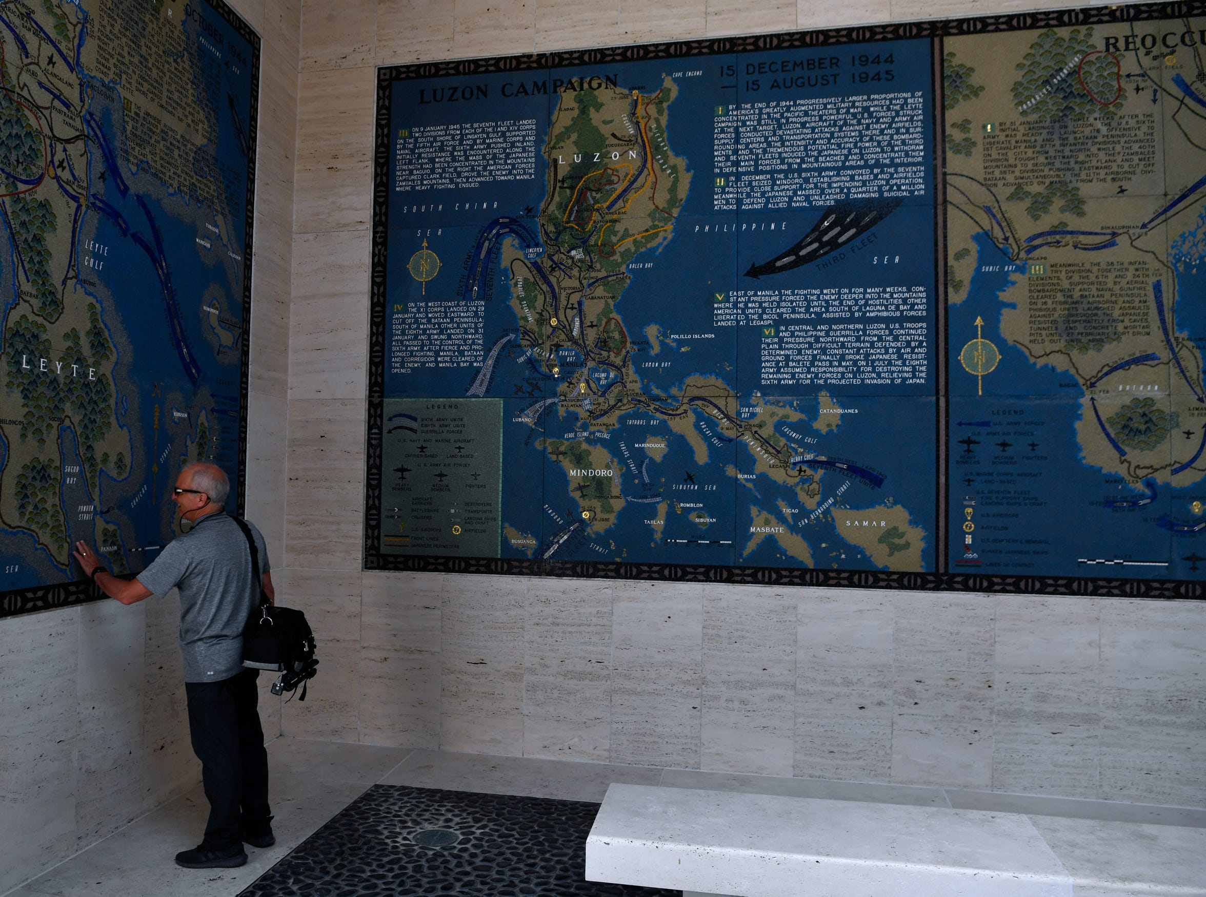 David Richter traces a hand over a mosaic map in one of the hemicycles at the Manila American Cemetery on Saturday. Richter is one of the architects who developed the site's new Visitor Center.