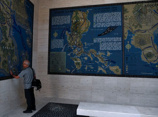 David Richter traces a hand over a mosaic map in one of the hemicycles at the Manila American Cemetery Saturday Oct. 19, 2019. Richter is one of the architects who developed the site's new Visitor Center.