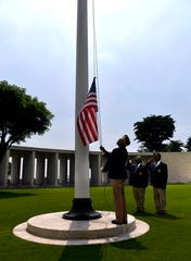 Carolyn Lewis lowers a flag after flying it over the Manila American Cemetery Friday Oct. 18, 2019. She was part of a small group from McDonough, Georgia who came to visit the grave of Willie B. Hatcher, the namesake of their VFW Post 516, and to attend the dedication of the cemetery's new Visitor Center.
