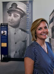 Amy Bachofen stands before a poster Saturday depicting her grandfather George Freed who was shot down near New Ireland during World War II, Oct. 19, 2019. Freed is one of the stories featured in the Manila American Cemetery's new Visitor Center.