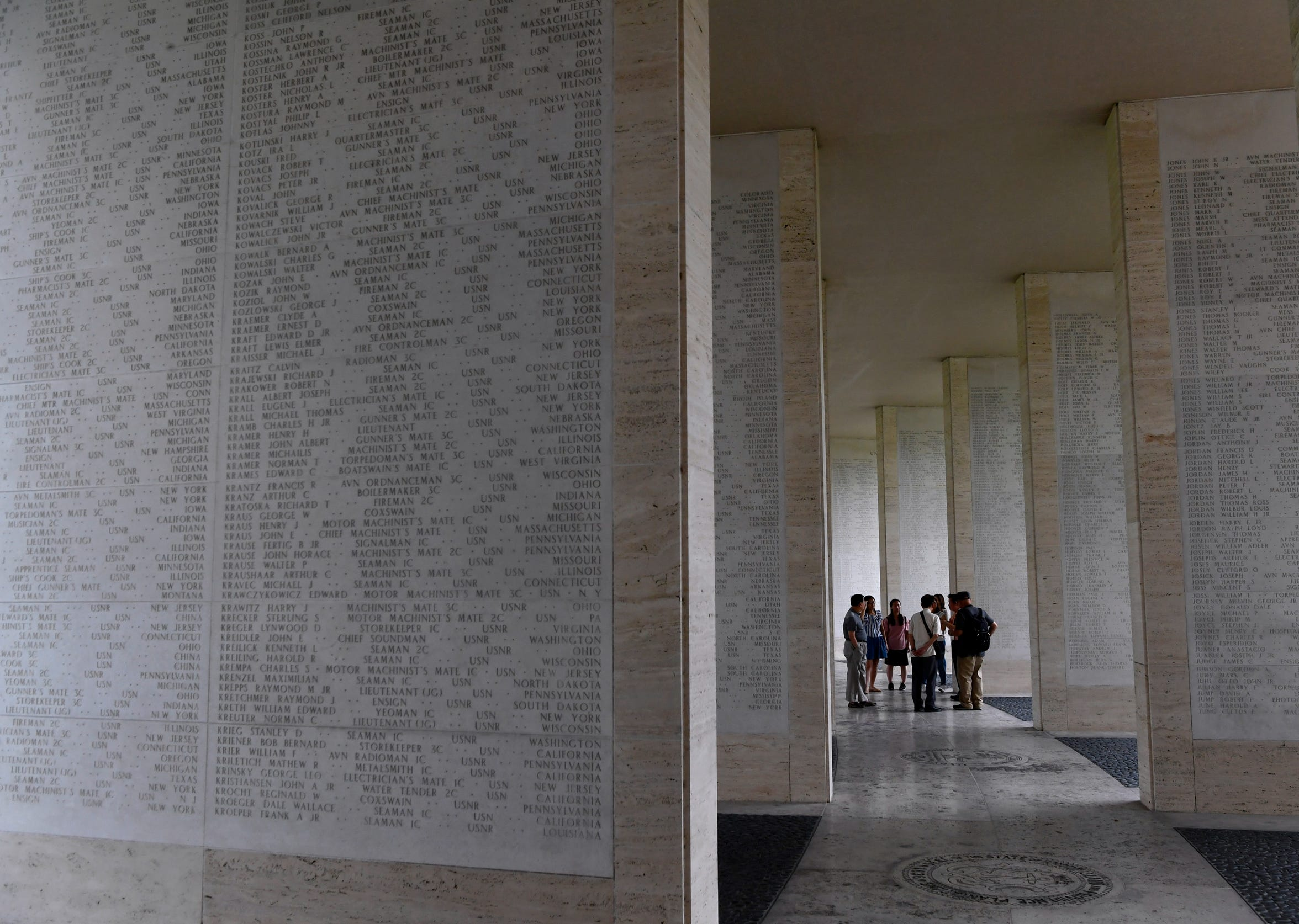 A group of visitors Saturday stands inside one of the hemicycles at Manila American Cemetery. The walls around them contain the names of more than 36,000 World War II missing service members.