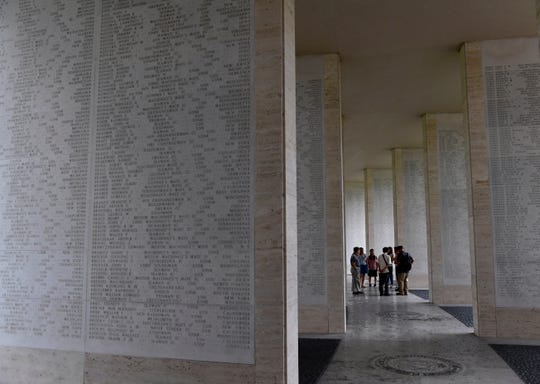 A group of visitors stands inside one of the hemicycles at the Manila American Cemetery Saturday Oct. 19, 2019. The walls around them contain the names of over 36,000 World War II missing service members.