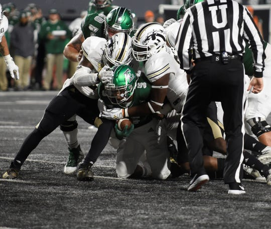 Eastern Michigan running back Shaq Vann is brought down by Western Michigan defenders on Saturday, Oct. 19, 2019 at Rynearson Stadium in Ypsilanti, Mich.