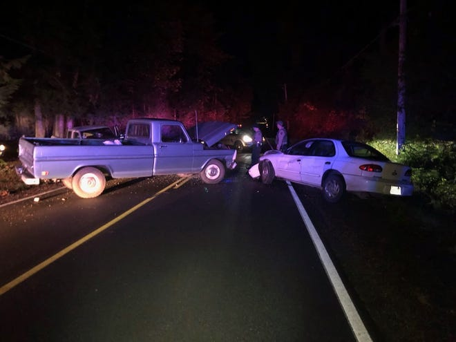 Kitsap County Sheriff's Office deputies investigate a crash involving two pickups and a sedan on Friday on Pioneer Way NW in North Kitsap.