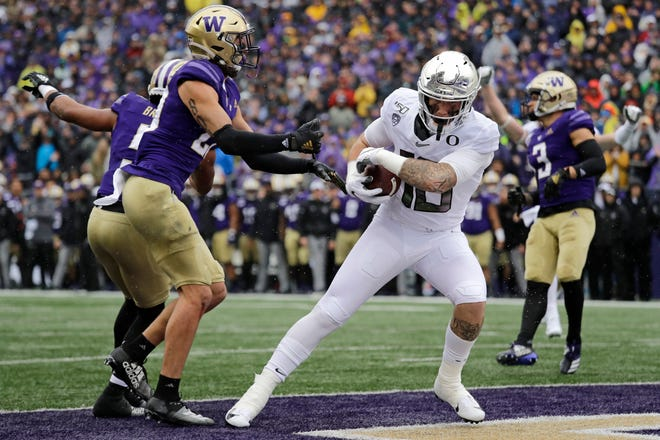 Oregon's Spencer Webb scores a touchdown as Washington's Asa Turner defends in the first half of an NCAA college football game Saturday, Oct. 19, 2019, in Seattle.