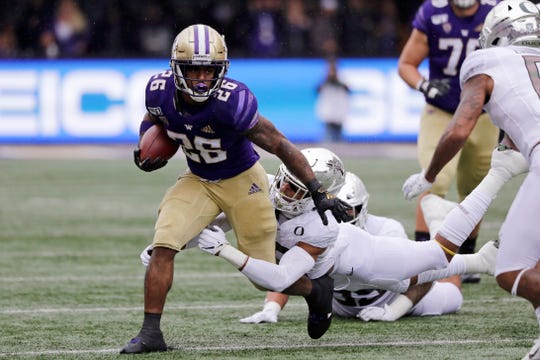 Washington's Salvon Ahmed (26) is tackled by Oregon's Nick Pickett in the first half of an NCAA college football game Saturday, Oct. 19, 2019, in Seattle.