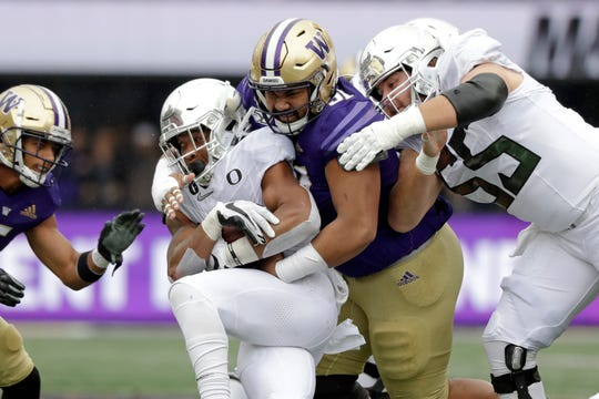 Washington's Tuli Letuligasenoa, center, tackles CJ Verdell as Oregon's Jake Hanson, right, moves in behind in the first half of an NCAA college football game Saturday, Oct. 19, 2019, in Seattle.