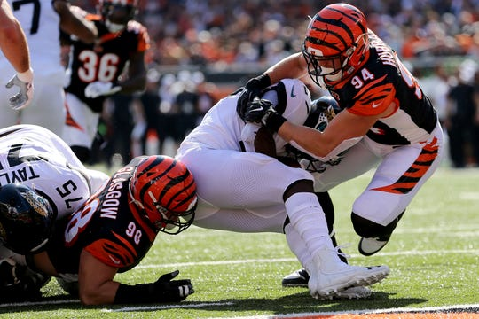 Cincinnati Bengals defensive end Sam Hubbard (94) and defensive tackle Ryan Glasgow (98) tackle Jacksonville Jaguars running back Leonard Fournette (27) near the goal line in the first quarter during a Week 7 NFL football game, Sunday, Oct. 20, 2019, at Paul Brown Stadium in Cincinnati.