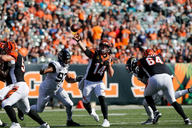 Cincinnati Bengals quarterback Andy Dalton (14) throws a pass under pressure from Jacksonville Jaguars defensive end Calais Campbell (93) in the third quarter of the NFL Week 7 game between the Cincinnati Bengals and the Jacksonville Jaguars at Paul Brown Stadium in downtown Cincinnati on Sunday, Oct. 20, 2019. The Bengals fell to 0-7 on the season with a 27-17 loss at home.