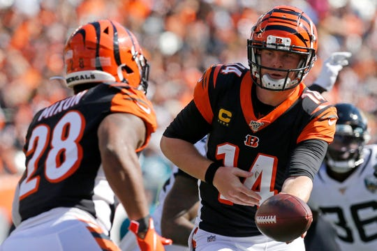 Cincinnati Bengals quarterback Andy Dalton (14) hands off to running back Joe Mixon (28) in the second quarter of the NFL Week 7 game between the Cincinnati Bengals and the Jacksonville Jaguars at Paul Brown Stadium in downtown Cincinnati on Sunday, Oct. 20, 2019.