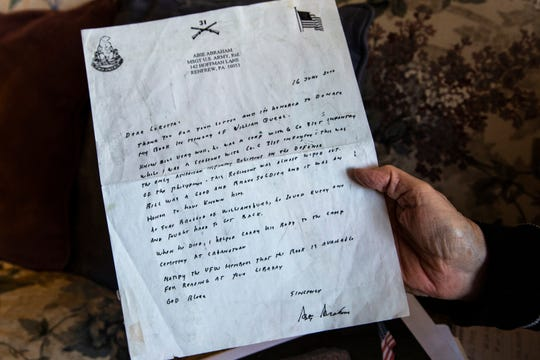 """Marilea Schmidt displays a letter from Abie Abraham about her uncle William """"Bill"""" Querl from a folder of images from his time enlisted, Thursday, Oct., 17, 2019, at her apartment in Marion, Iowa."""