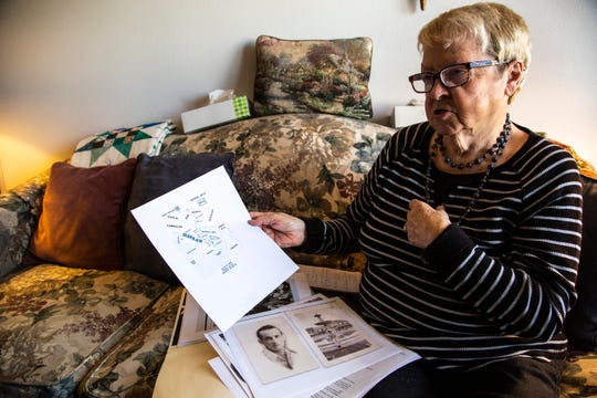 """Marilea Schmidt speaks about the Bataan Death March, while looking through photos of her uncle William """"Bill"""" Querl from a folder of images, Thursday, Oct., 17, 2019, at her apartment in Marion, Iowa."""
