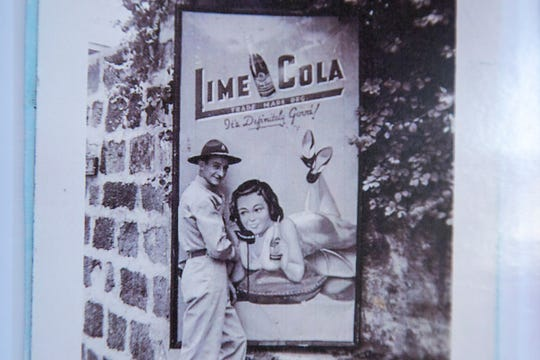 """William """"Bill"""" Querl poses for a photo with an advertisement for Lime Cola, photographed, Thursday, Oct., 17, 2019, at the apartment of his niece, Marilea Schmidt, in Marion, Iowa."""