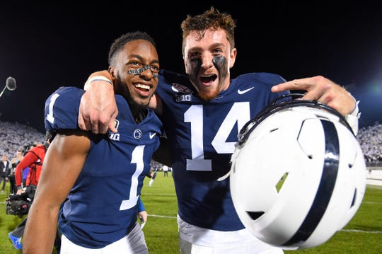Penn State receiver KJ Hamler (1) and quarterback Sean Clifford celebrate the win against Michigan.