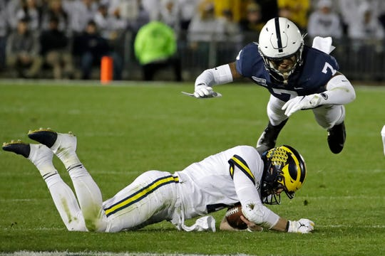 Penn State safety Jaquan Brisker leaps to avoid a sliding Michigan quarterback Shea Patterson at the end of a scramble for a first down during the first half in State College, Pa., Saturday, Oct. 19, 2019.