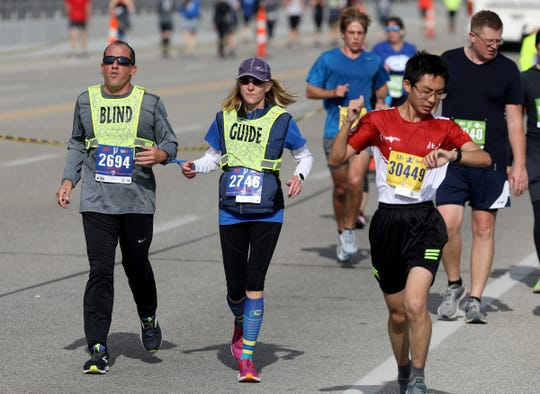 Michigan Supreme Court Justice Richard Bernstein and his guide Sara Reichert head across the MacArthur Bridge going onto Belle Isle mile 20 during the 42nd Annual Detroit Free Press/TCF Bank Marathon in Detroit on Sunday, Oct. 20, 2019.