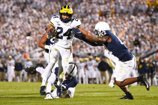 Michigan running back Zach Charbonnet runs with the ball as Penn State safety Garrett Taylor (17) defends during the third quarter at Beaver Stadium, Oct. 19, 2019.