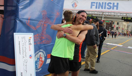 Detroit Free Press/TCF Bank Marathon runner-up Bryan Burk (left) hugs third-place finisher Samuel Skeels in the finish chute on Fort St. Both were happy to run their personal-record times on Sunday, Oct. 20, 2019.