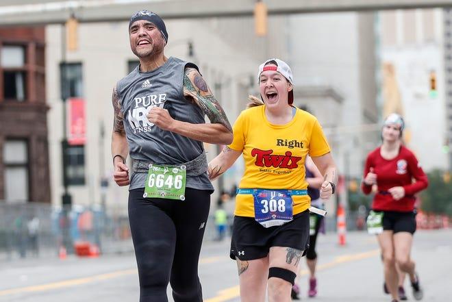 Marathoner Carlos Orosco of Saginaw, left, and Katelyn Trepkowski, also of Saginaw, cross the finish line during the 42nd Annual Detroit Free Press/TCF Bank Marathon in Detroit on Sunday, Oct. 20, 2019.